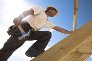 Dachdecker mit Hammer auf Dach