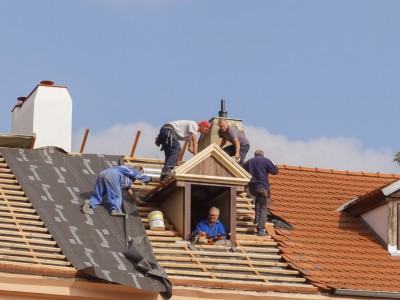 Prague, Czech Republic - October 3, 2014: Men roofers on the roof make waterproofing and put tile.